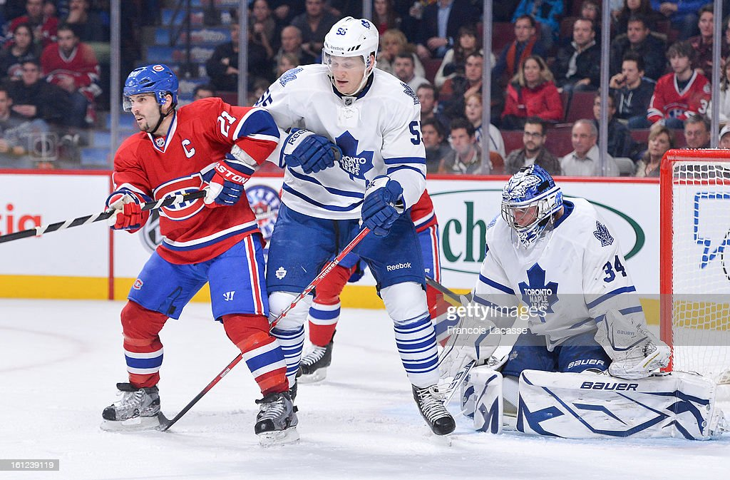 Brian Gionta #21 of the Montreal Canadiens and Korbinian Holzer #55 of the Toronto Maple Leafs battle for position in front of goalie James Reimer #34 during the NHL game on February 9, 2013 at the Bell Centre in Montreal, Quebec, Canada.