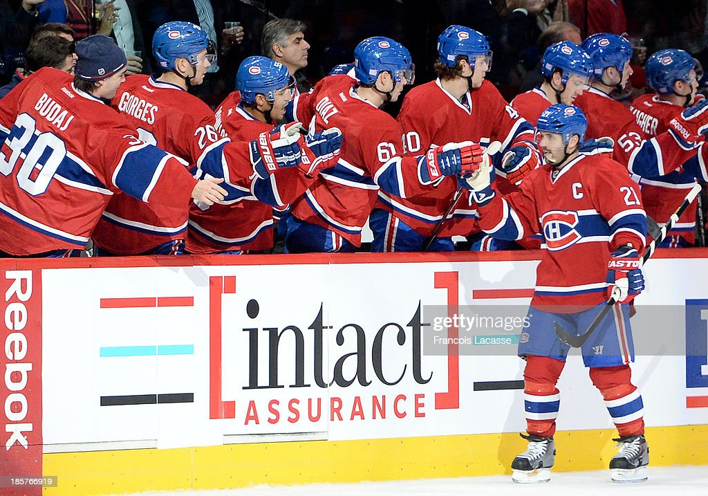 Brian Gionta #21 of the Montreal Canadiens celebrates with teammates Josh Gorges #26, Francis Bouillon #55 and Raphael Diaz #61 after scoring a goal against the Anaheim Ducks in the second period during the NHL game on October 24, 2013 at the Bell Centre in Montreal, Quebec, Canada.