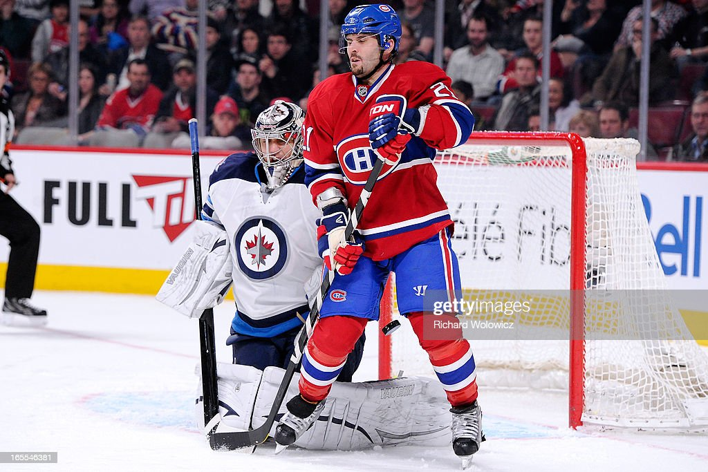 <a gi-track='captionPersonalityLinkClicked' href=/galleries/search?phrase=Brian+Gionta&family=editorial&specificpeople=202116 ng-click='$event.stopPropagation()'>Brian Gionta</a> #21 of the Montreal Canadiens deflects the puck past Ondrej Pavelec #31 of the Winnipeg Jets to score during the NHL game at the Bell Centre on April 4, 2013 in Montreal, Quebec, Canada.