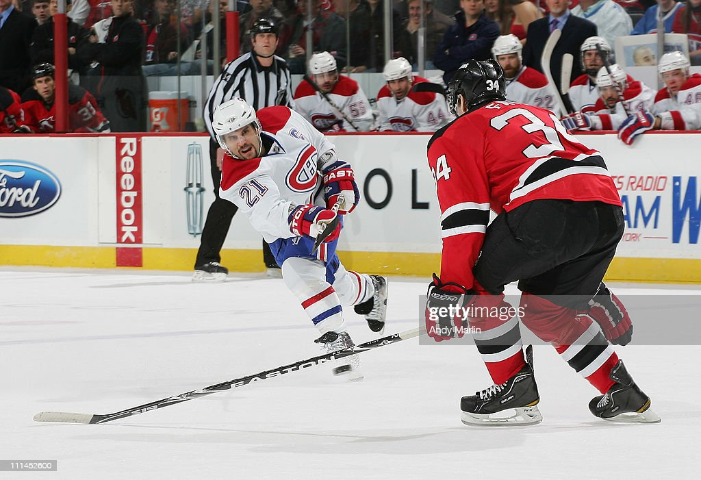 <a gi-track='captionPersonalityLinkClicked' href=/galleries/search?phrase=Brian+Gionta&family=editorial&specificpeople=202116 ng-click='$event.stopPropagation()'>Brian Gionta</a> #21 of the Montreal Canadiens fires a shot while being defended by Mark Fayne #34 of the New Jersey Devils during the game at the Prudential Center on April 2, 2011 in Newark, New Jersey.