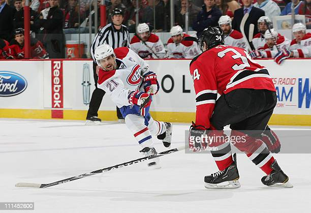 Brian Gionta of the Montreal Canadiens fires a shot while being defended by Mark Fayne of the New Jersey Devils during the game at the Prudential...
