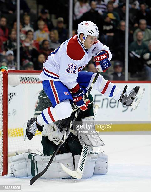 Brian Gionta of the Montreal Canadiens gets out of the way of a shot stopped by Josh Harding of the Minnesota Wild during the second period of the...