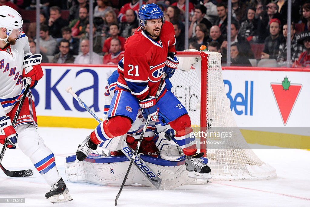 Brian Gionta #21 of the Montreal Canadiens jumps to avoid the incoming puck in front of Cam Talbot #33 of the New York Rangers during the NHL game at the Bell Centre on April 12, 2014 in Montreal, Quebec, Canada.