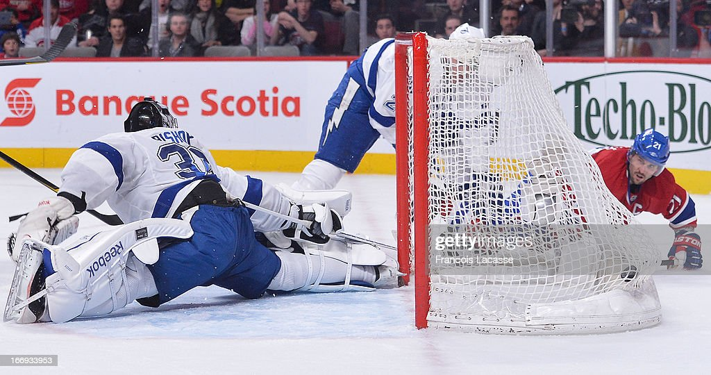<a gi-track='captionPersonalityLinkClicked' href=/galleries/search?phrase=Brian+Gionta&family=editorial&specificpeople=202116 ng-click='$event.stopPropagation()'>Brian Gionta</a> #21 of the Montreal Canadiens looks as the puck enters the net behind goalie <a gi-track='captionPersonalityLinkClicked' href=/galleries/search?phrase=Ben+Bishop&family=editorial&specificpeople=700137 ng-click='$event.stopPropagation()'>Ben Bishop</a> #30 of the Tampa Bay Lightning in NHL action on April 18, 2013 at the Bell Centre in Montreal, Quebec, Canada.