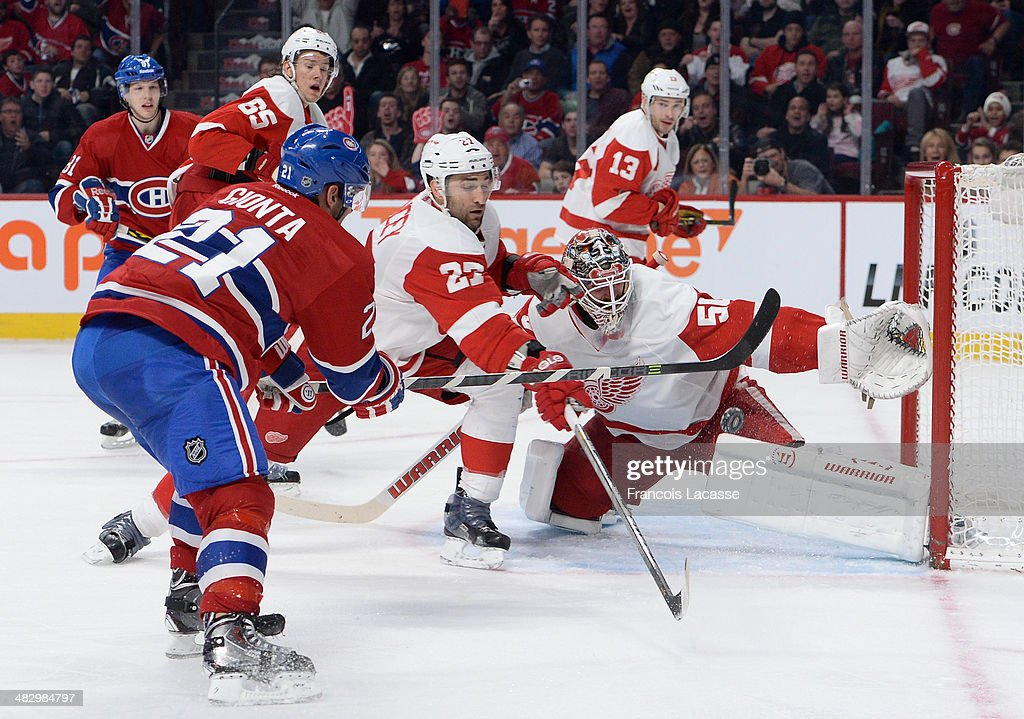 <a gi-track='captionPersonalityLinkClicked' href=/galleries/search?phrase=Brian+Gionta&family=editorial&specificpeople=202116 ng-click='$event.stopPropagation()'>Brian Gionta</a> #21 of the Montreal Canadiens slaps a shot against <a gi-track='captionPersonalityLinkClicked' href=/galleries/search?phrase=Jonas+Gustavsson&family=editorial&specificpeople=886789 ng-click='$event.stopPropagation()'>Jonas Gustavsson</a> #50 while being challenged by <a gi-track='captionPersonalityLinkClicked' href=/galleries/search?phrase=Kyle+Quincey&family=editorial&specificpeople=2234340 ng-click='$event.stopPropagation()'>Kyle Quincey</a> #27 of the Detroit Red Wings during the NHL game on April 5, 2014 at the Bell Centre in Montreal, Quebec, Canada.
