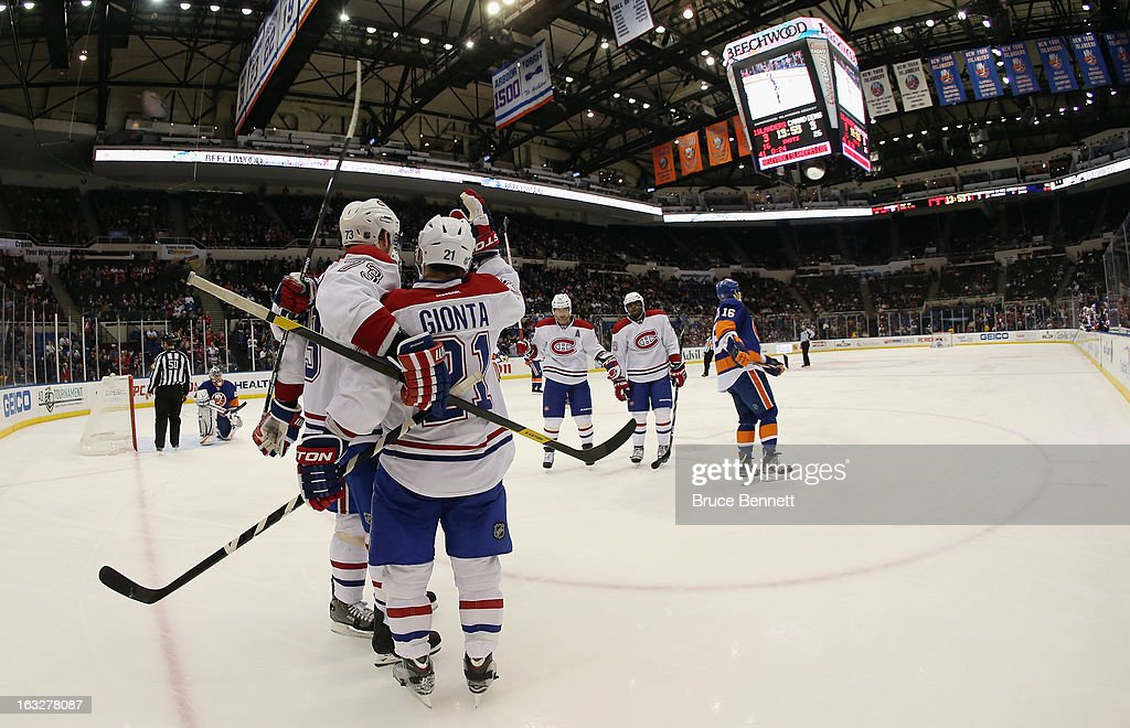 <a gi-track='captionPersonalityLinkClicked' href=/galleries/search?phrase=Brian+Gionta&family=editorial&specificpeople=202116 ng-click='$event.stopPropagation()'>Brian Gionta</a> #21 of the Montreal Canadiens sores a powerplay goal at 6:07 of the third period against the New York Islanders and is joined by <a gi-track='captionPersonalityLinkClicked' href=/galleries/search?phrase=Michael+Ryder&family=editorial&specificpeople=208983 ng-click='$event.stopPropagation()'>Michael Ryder</a> #73 at the Nassau Veterans Memorial Coliseum on March 5, 2013 in Uniondale, New York. The Islanders defeated the Canadiens 6-3. The goal was the 20,000th in the Montreal Canadiens history.
