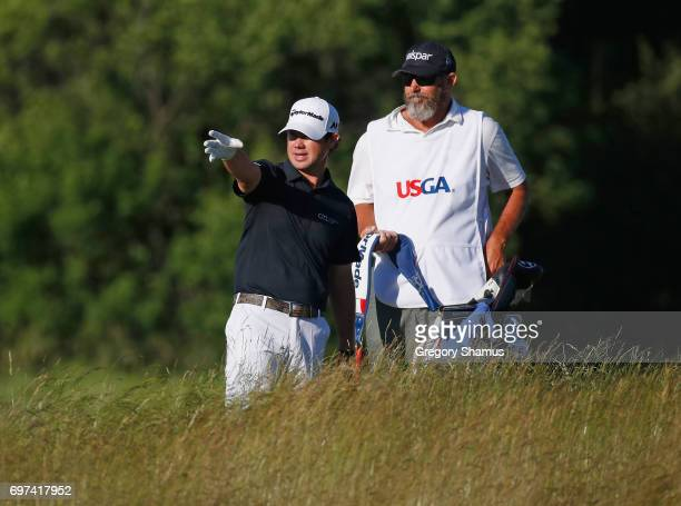 Brian Harman of the United States and caddie Scott Tway discuss a shot on the 15th hole during the final round of the 2017 US Open at Erin Hills on...