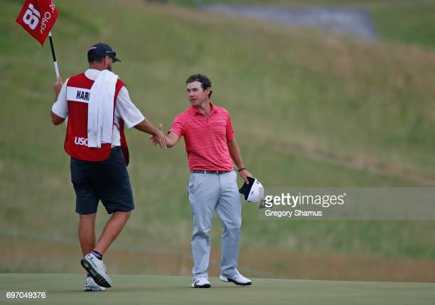 Brian Harman of the United States and caddie Scott Tway shake hands after finishing on the 18th green during the third round of the 2017 US Open at...