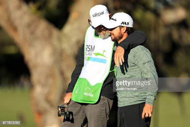 Brian Harman of the United States talks with his caddie after putting on the 18th green during the final round of The RSM Classic at Sea Island Golf...