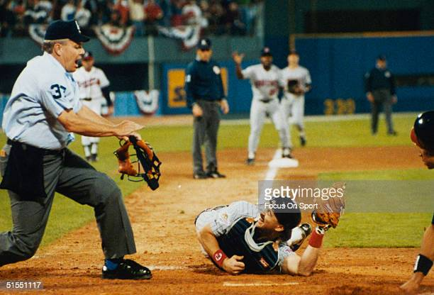 Brian Harper of the Minnesota Twins shows the ball to the umpire after a play at home plate during the World Series against the Atlanta Braves during...