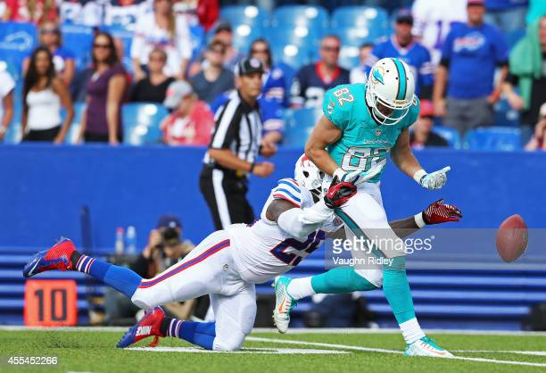 Brian Hartline of the Miami Dolphins has a pass broken up by Da'Norris Searcy of the Buffalo Bills during the second half at Ralph Wilson Stadium on...