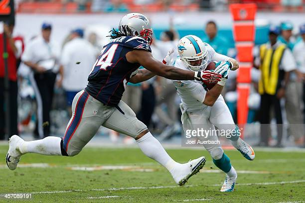 Brian Hartline of the Miami Dolphins is tackled by Dont'a Hightower of the New England Patriots on December 15 2013 at Sun Life Stadium in Miami...