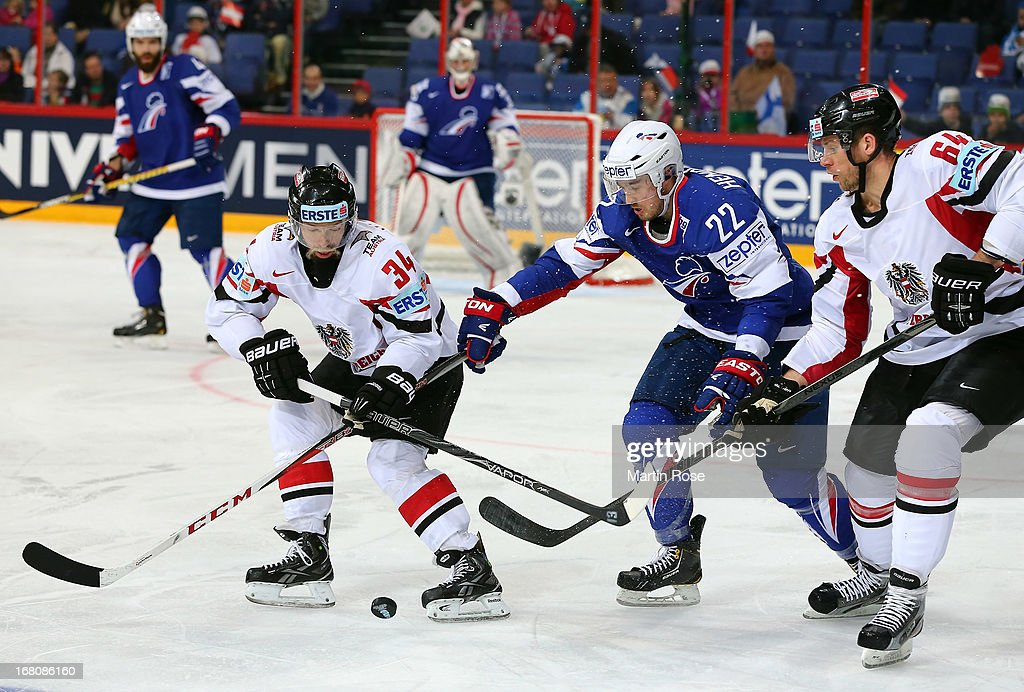 Brian Henderson (C) of France and Markus Peitner (L) and Andre Lakos (R) of Austria battle for the puck during the IIHF World Championship group H match between France and Austria at Hartwall Areena on May 5, 2013 in Helsinki, Finland.