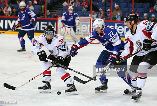 Brian Henderson of France and Markus Peitner and Andre Lakos of Austria battle for the puck during the IIHF World Championship group H match between...