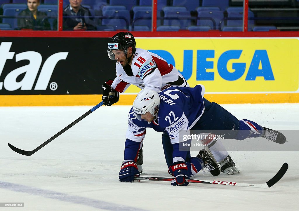 Brian Henderson (R) of France and Thomas Koch (L) of Austria battle for the puck during the IIHF World Championship group H match between France and Austria at Hartwall Areena on May 5, 2013 in Helsinki, Finland.
