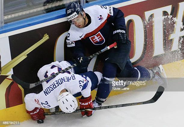 Brian Henderson of France is checked by Karol Sloboda of Slovakia during the 2014 IIHF World Championship between France and Slovakia at Chizhovka...