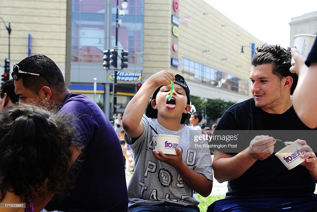 Brian Iraheta, 12, of Columbus, Ohio, eats a gummy worm from his frozen yogurt next to his cousin, right, Oscar Ramirez, 23, of Lorton, VA in Washington, DC on June 25, 2013.