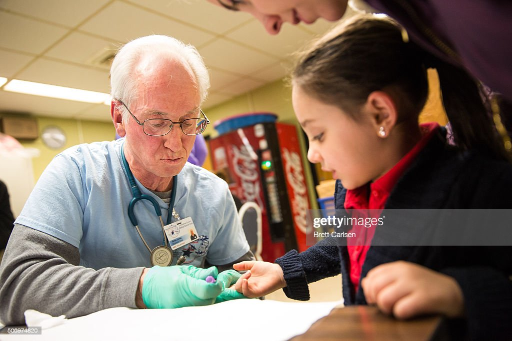 Brian Jones, a first responder for Livingston County Michigan, draws the blood of Amaria Roberson, age 5 of Flint, to screen her blood for lead on January 26, 2016 at Eisenhower Elementary School in Flint, Michigan. Free lead screenings are performed for Flint children 6-years-old and younger, one of several events sponsored by Molina Healthcare following the city's water contamination and federal state of emergency.