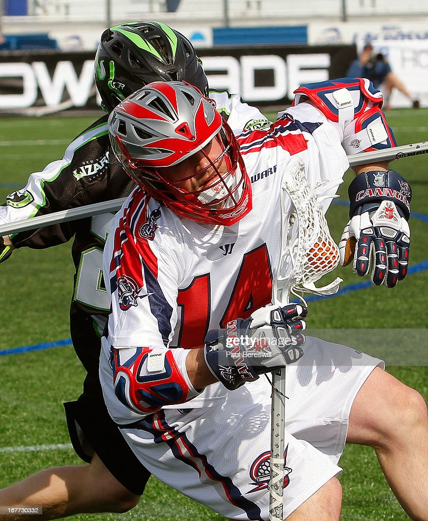 Brian Karalunas #25 of the New York Lizzards checks Ryan Boyle #14 of the Boston Cannons in the second half of a Major League Lacrosse game at James M. Shuart Stadium on April 28, 2013 in Hempstead, New York.