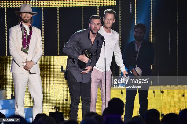 Brian Kelley of Florida Georgia Line director TK McKamy and Tyler Hubbard of Florida Georgia Line accept an award onstage during the 2017 CMT Music...