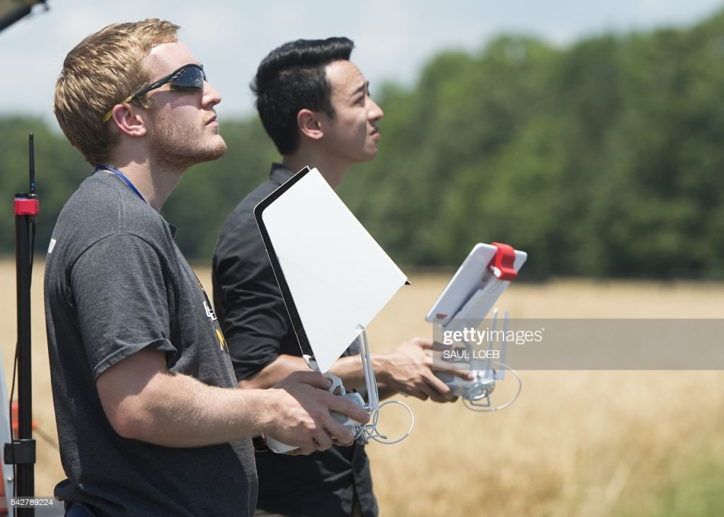 Brian Kelly, an aerospace engineering student at the University of Maryland (UMD), and Ryan Wong (R), an electrical engineering student at UMD, together control the flying and cameras of a DJI Inspire drone at a testing site for the University of Maryland's Unmanned Aircraft Systems (UAS) programs in Bushwood, Maryland, June 24, 2016. The Federal Aviation Administration has unveiled new rules that clear the way for small, commercial drones to operate across US airspace. Drone operators will be allowed to fly commercial craft weighing less than 55 pounds (25 kilograms) during daylight hours, provided they can maintain a clear view of the drone at all times. / AFP / SAUL