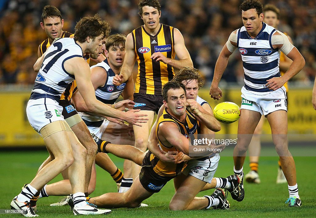 Brian Lake of the Hawks handballs whilst being tackled by Mitch Duncan of the Cats during the AFL First Preliminary FInal match between the Hawthorn Hawks and the Geelong Cats at the Melbourne Cricket Ground on September 20, 2013 in Melbourne, Australia.