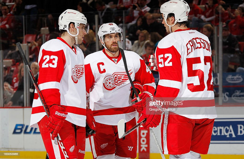 Brian Lashoff #23, Henrik Zetterberg #40 and Jonathan Ericsson #52 of the Detroit Red Wings talk things over during a game against the Nashville Predators at Joe Louis Arena on February 23, 2013 in Detroit, Michigan. Detroit won the game 4-0.