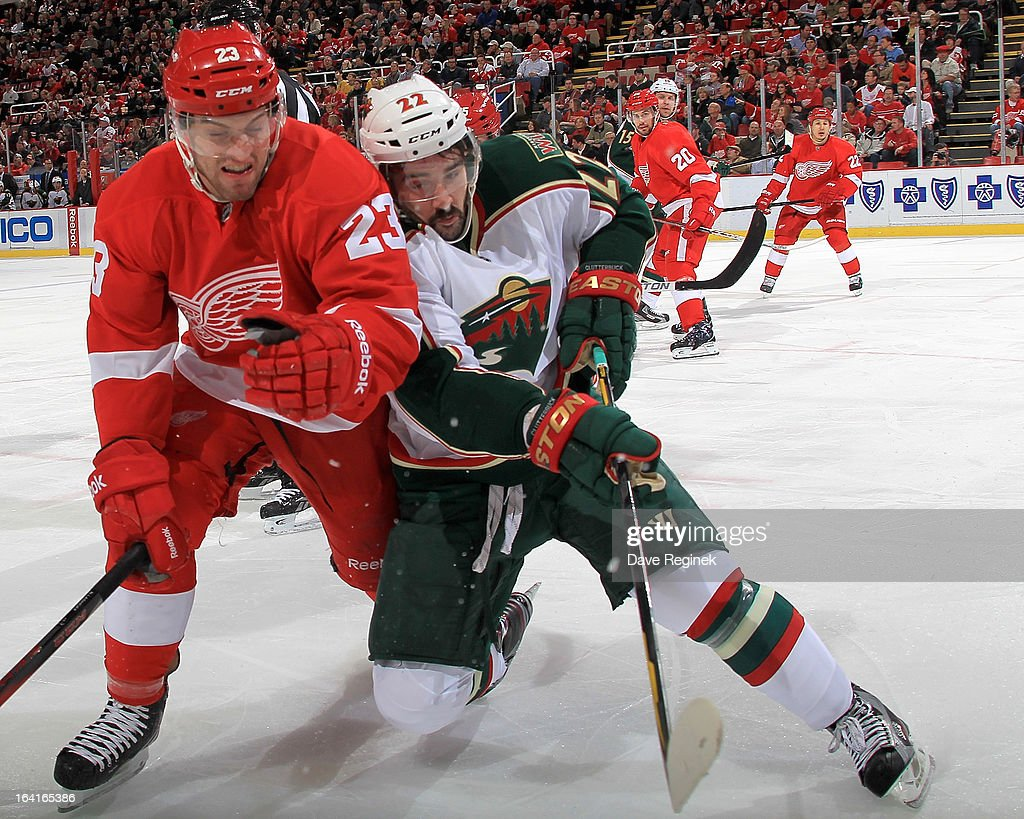 Brian Lashoff #23 of the Detroit Red Wings and Cal Clutterbuck #22 of the Minnesota Wild go hard into the boards during a NHL game at Joe Louis Arena on March 20, 2013 in Detroit, Michigan.