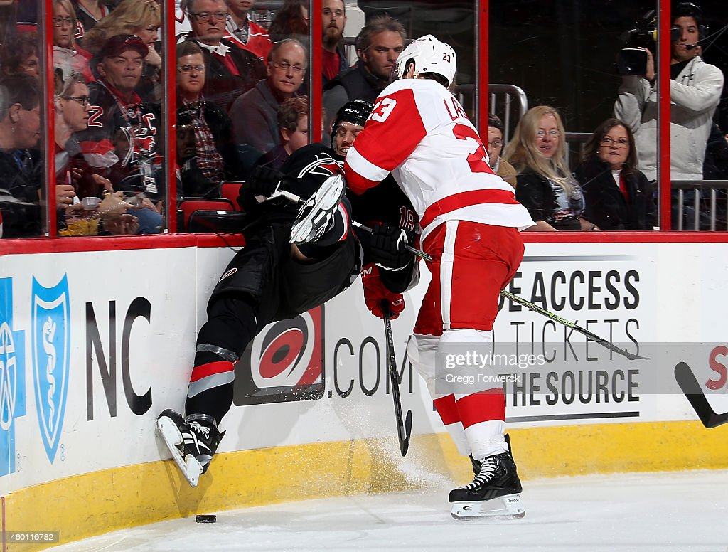 <a gi-track='captionPersonalityLinkClicked' href=/galleries/search?phrase=Brian+Lashoff&family=editorial&specificpeople=5529056 ng-click='$event.stopPropagation()'>Brian Lashoff</a> #23 of the Detroit Red Wings collides along the boards with Jat McClement #18 of the Carolina Hurricanes during their NHL game at PNC Arena on December 7, 2014 in Raleigh, North Carolina.