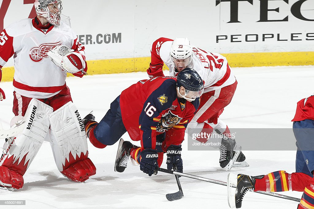 <a gi-track='captionPersonalityLinkClicked' href=/galleries/search?phrase=Brian+Lashoff&family=editorial&specificpeople=5529056 ng-click='$event.stopPropagation()'>Brian Lashoff</a> #23 of the Detroit Red Wings upends <a gi-track='captionPersonalityLinkClicked' href=/galleries/search?phrase=Aleksander+Barkov&family=editorial&specificpeople=8760147 ng-click='$event.stopPropagation()'>Aleksander Barkov</a> #16 of the Florida Panthers as he skates past goaltender <a gi-track='captionPersonalityLinkClicked' href=/galleries/search?phrase=Jimmy+Howard&family=editorial&specificpeople=2118637 ng-click='$event.stopPropagation()'>Jimmy Howard</a> #35 at the BB&T Center on December 10, 2013 in Sunrise, Florida. The Panthers defeated the red Wings 3-2 in a shootout.