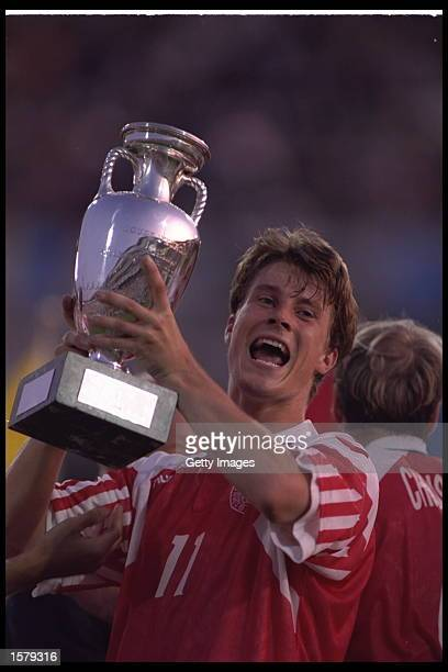 Brian Laudrup of Denmark holds aloft the European nations trophy after his team defeats Germany by 20 in the final in Gothenburg Sweden 1992...