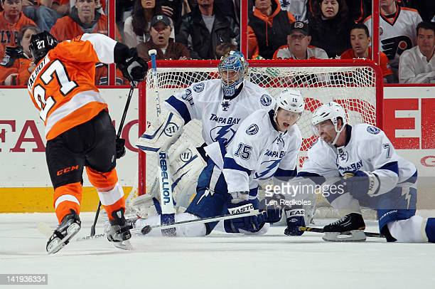 Brian Lee and Brett Clark of the Tampa Bay Lightning block a shot on goaltender Dwayne Roloson by Max Talbot of the Philadelphia Flyers on March 26...