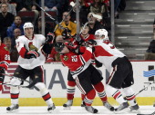 Brian Lee of the Ottawa Senators pushes into Viktor Stalberg of the Chicago Blackhawks as teammate Filip Kuba watches from behind on January 7 2011...