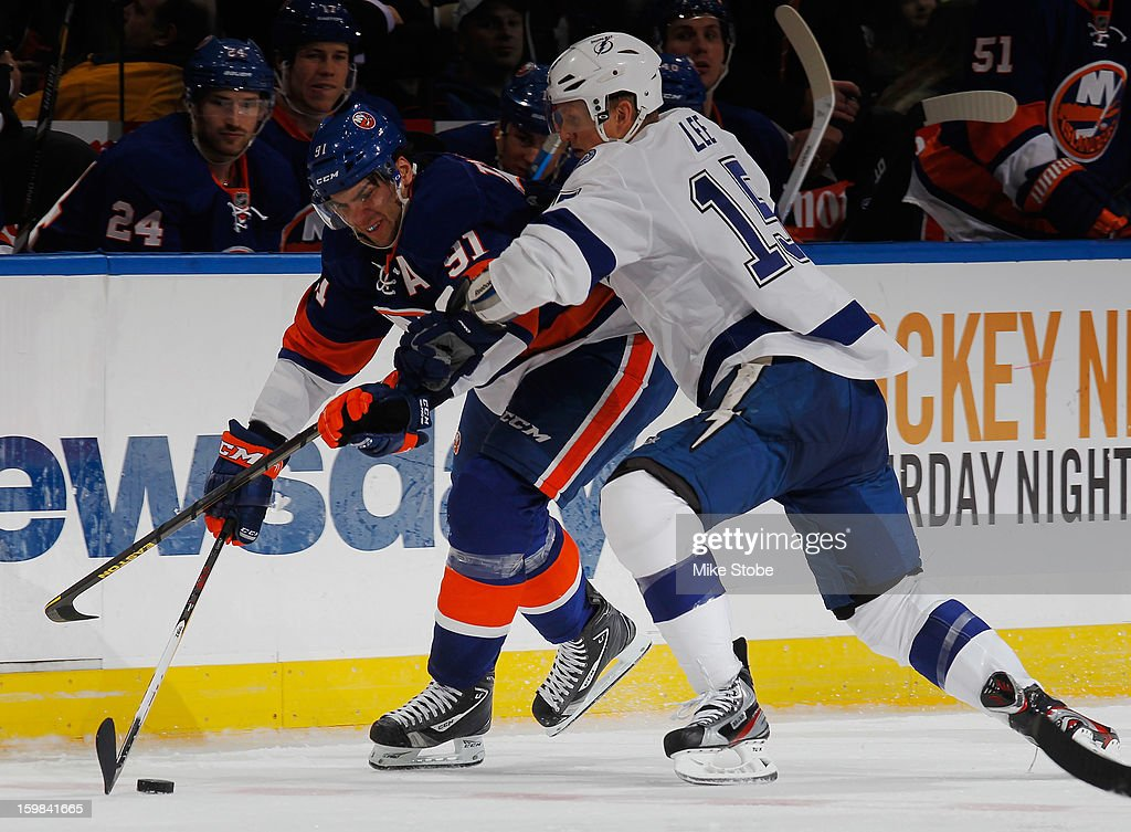 Brian Lee #15 of the Tampa Bay Lightning is held off by John Tavares #91 of the New York Islanders at Nassau Veterans Memorial Coliseum on January 21, 2013 in Uniondale, New York. The Islanders defeated the Lightning 4-3.