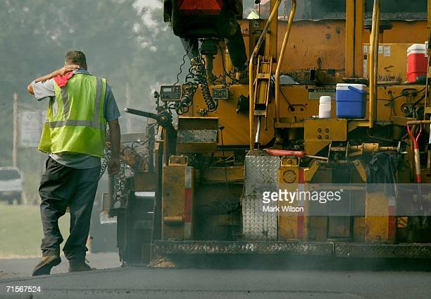 Brian Loy deals with the heat while working with a crew paving a highway August 2 2006 in Huntingtown Maryland A Code Red warning is in effect for...