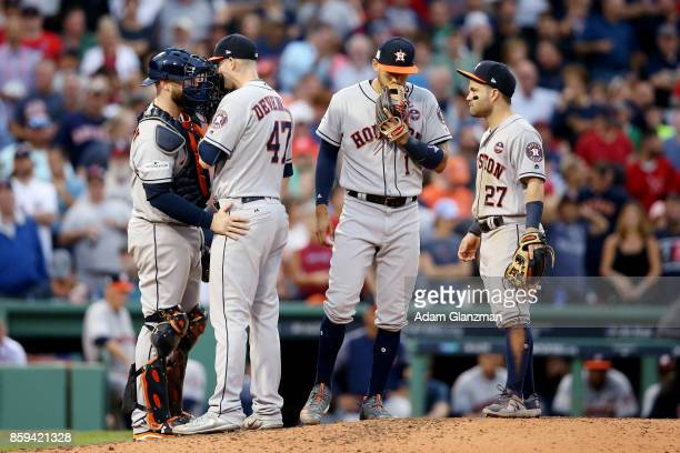 Brian McCann and Chris Devenski of the Houston Astros meet on the mound as Carlos Correa and Jose Altuve look on during Game 3 of the American League...