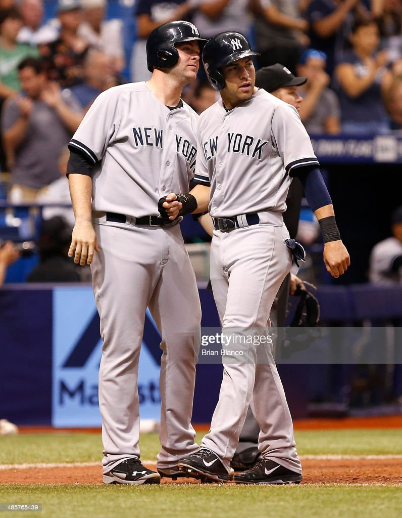 Brian McCann #34 (L) and Jacoby Ellsbury #22 of the New York Yankees celebrate at the plate as they score off of a Carlos Beltran two-run single during the top of the 12th inning of a game against the Tampa Bay Rays on April 20, 2014 at Tropicana Field in St. Petersburg, Florida.
