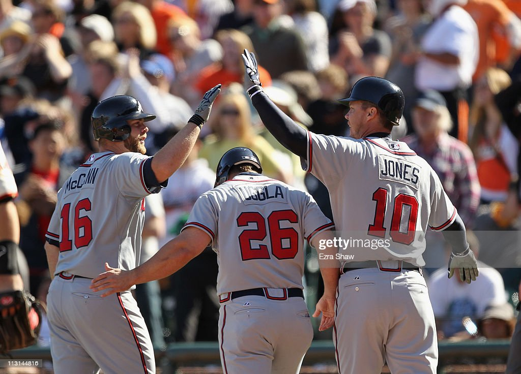 Brian McCann Dan Uggla and Chipper Jones of the Atlanta Braves celebrate after Uggla and Jones scored in the 10th inning against the San Francisco...