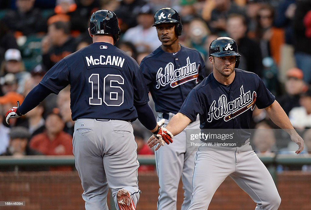<a gi-track='captionPersonalityLinkClicked' href=/galleries/search?phrase=Brian+McCann+-+Baseball+Player&family=editorial&specificpeople=593065 ng-click='$event.stopPropagation()'>Brian McCann</a> #16 of the Atlanta Braves is congratulated by <a gi-track='captionPersonalityLinkClicked' href=/galleries/search?phrase=Dan+Uggla&family=editorial&specificpeople=542208 ng-click='$event.stopPropagation()'>Dan Uggla</a> #26 (R) and <a gi-track='captionPersonalityLinkClicked' href=/galleries/search?phrase=B.J.+Upton&family=editorial&specificpeople=810704 ng-click='$event.stopPropagation()'>B.J. Upton</a> #2 (C) after McCann hit a two-run homer against the San Francisco Giants in the second inning at AT&T Park on May 9, 2013 in San Francisco, California. Uggla scored in front of McCann on the homer.