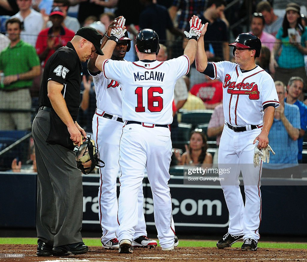 Brian McCann #16 of the Atlanta Braves is congratulated by Kris Medlen #54 and Justin Upton #8 after hitting a three run home run in the third inning against the Cleveland Indians at Turner Field on August 29, 2013 in Atlanta, Georgia.
