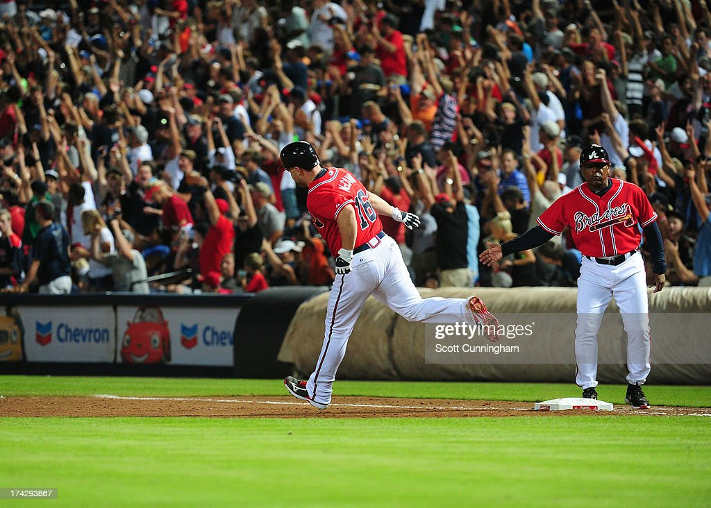 Brian McCann #16 of the Atlanta Braves is congratulated by Terry Pendleton #9 after hitting a seventh inning home run against the Cincinnati Reds at Turner Field on July 12, 2013 in Atlanta, Georgia.