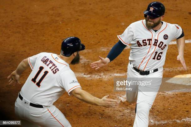 Brian McCann of the Houston Astros celebrates with Evan Gattis after scoring off of a single hit by Jose Altuve against Luis Severino of the New York...