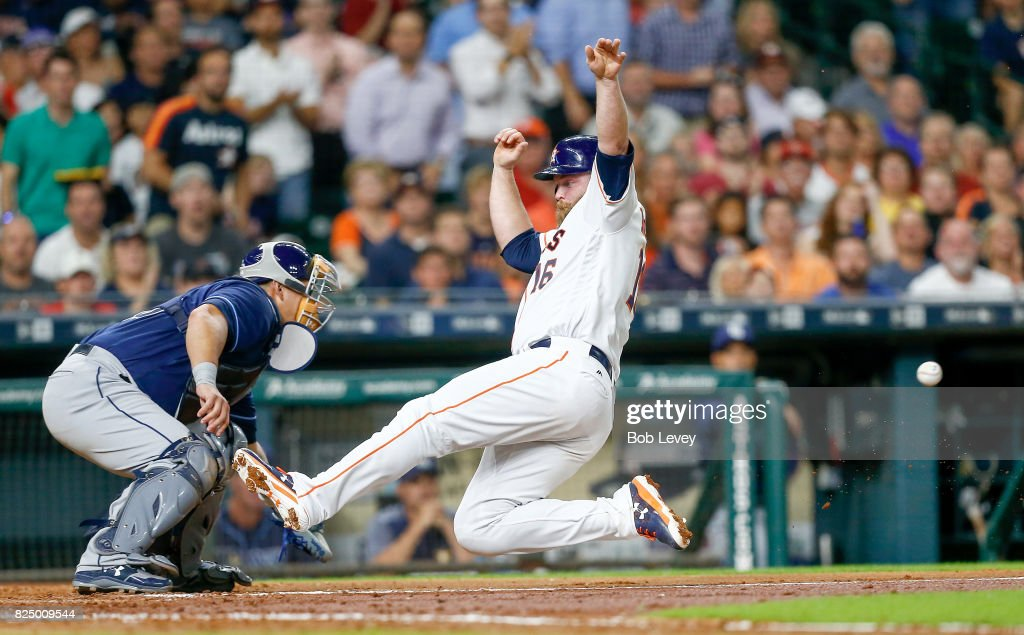 Brian McCann #16 of the Houston Astros scores in the third inning as Wilson Ramos #40 of the Tampa Bay Rays is unable to make the tag at Minute Maid Park on July 31, 2017 in Houston, Texas.