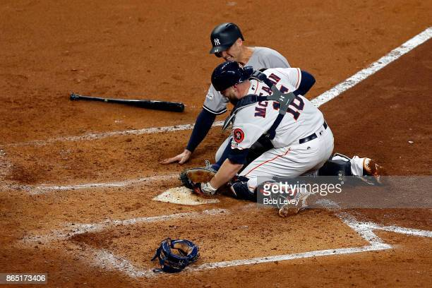Brian McCann of the Houston Astros tags out Greg Bird of the New York Yankees at home plate during the fifth inning in Game Seven of the American...
