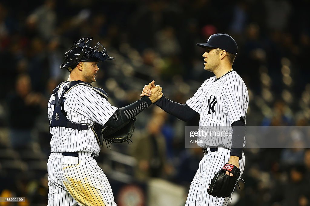 Brian McCann #34 of the New York Yankees celebrates a 4-1 win with David Phelps #41 against the Boston Red Sox at Yankee Stadium on April 10, 2014 in the Bronx borough of New York City.