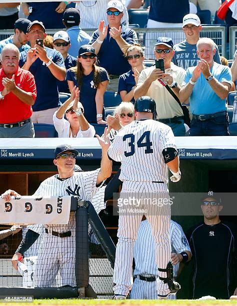 Brian McCann of the New York Yankees celebrates his first inning home run against the Cleveland Indians with manager Joe Girardi at Yankee Stadium on...