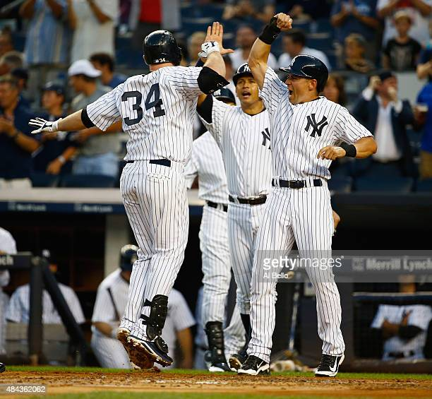 Brian McCann of the New York Yankees celebrates his first inning three run home run with Jacoby Ellsbury against the Minnesota Twins during their...
