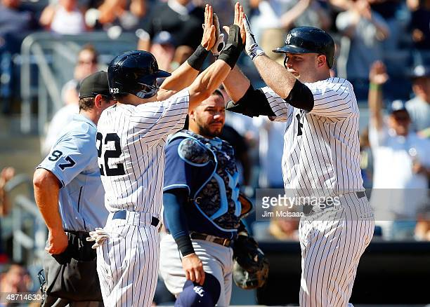 Brian McCann of the New York Yankees celebrates his game tying sixth inning three run home run with teammate Jacoby Ellsbury as Rene Rivera of the...