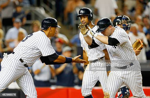 Brian McCann of the New York Yankees celebrates his seventh inning three run home run against the Boston Red Sox with teammates Alex Rodriguez and...