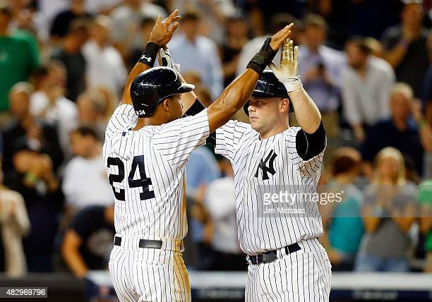 Brian McCann of the New York Yankees celebrates his seventh inning three run home run against the Boston Red Sox with teammate Chris Young at Yankee...
